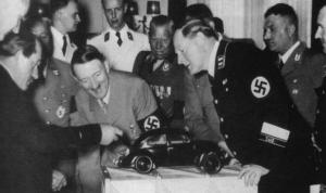 Ferdinand Porsche și Adolf Hitler examinează un model prototip care va evolua în Volkswagen Buburuza